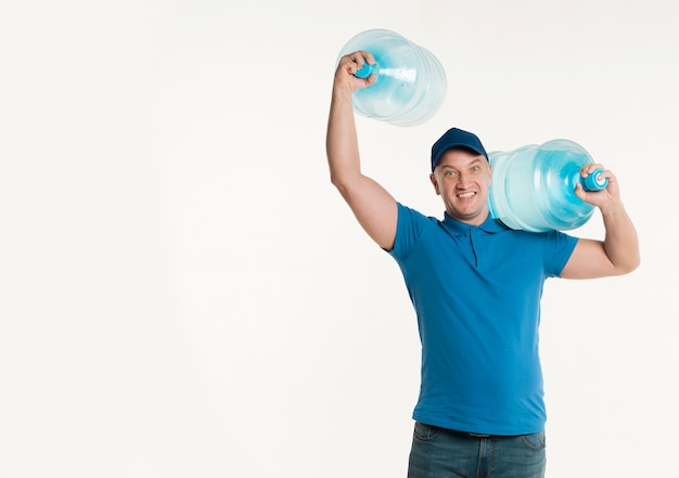 De leveringsmens van smiley het stellen met waterflessen en exemplaarruimte
