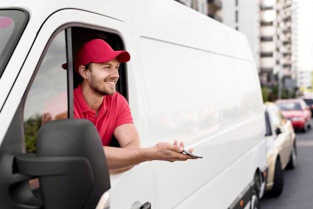 De leveringsmens van smiley in auto met mobiel