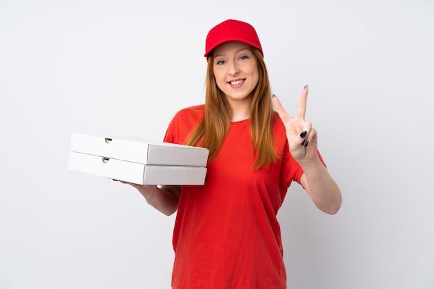 De leveringsvrouw die van de pizza een pizza over geïsoleerde roze muur houdt die en overwinningsteken glimlacht toont
