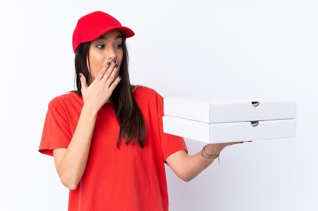 De leveringsvrouw die van de pizza een pizza over geïsoleerde witte muur met verrassing en geschokte gelaatsuitdrukking houdt