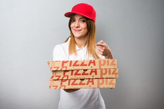 De leveringsvrouw die van de pizza iets op geweven achtergrond houdt