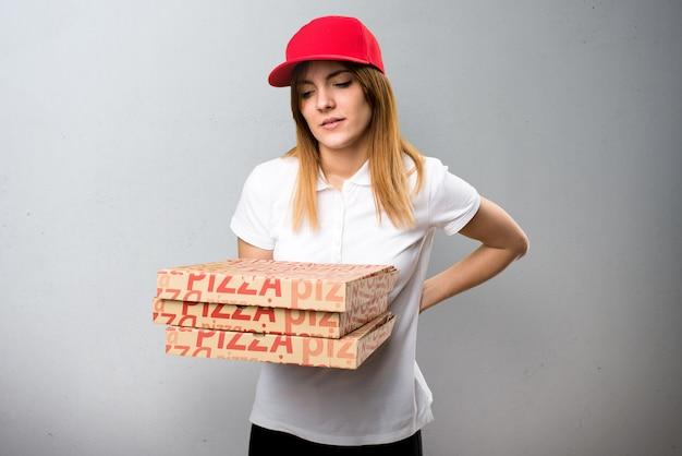 De leveringsvrouw van de pizza met rugpijn op geweven achtergrond