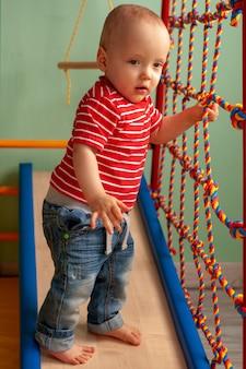 De lichamelijke ontwikkeling van het kind. kinder sport. kindergymnastiekcomplex thuis. oefening op de simulator. gezond kind, gezonde levensstijl