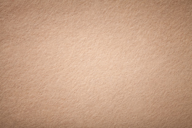 De lichtbruine matte close-up van de suèdestof. fluweeltextuur van gevoelde achtergrond