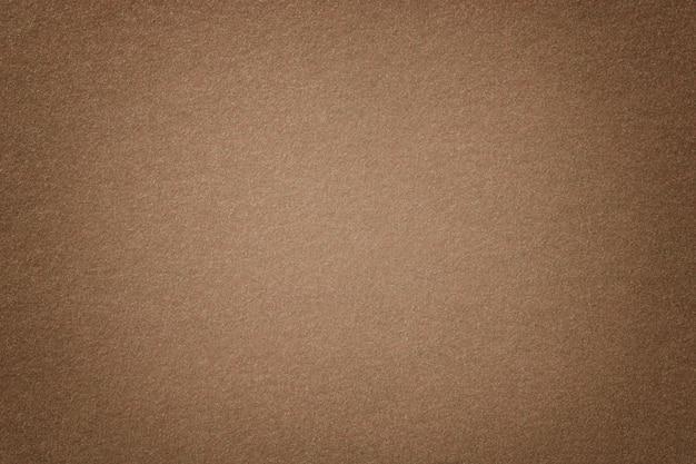 De lichtbruine matte close-up van de suèdestof. fluwelen textuur van vilt.