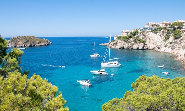 De lichten van een zon. zeilboot op zee, rotsen en blauwe lucht. sicilië, italië