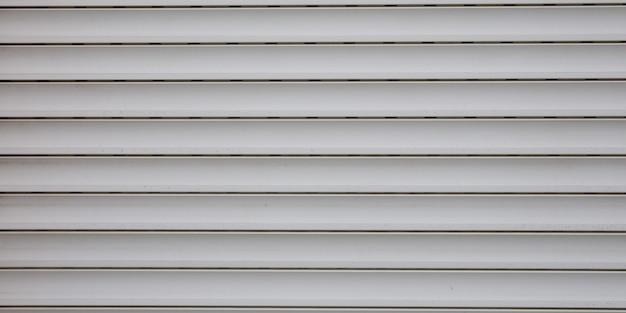 De lichtgrijze plastic achtergrond van de deur grijze panelen van het textuur metaalrolluik