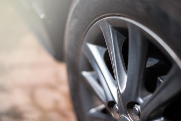 De lichtmetalen en zwarte banden van wielen hebben vuil stof met reflecterend helder licht