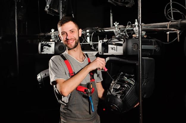 De lichttechnicus repareert het lichtapparaat op het podium
