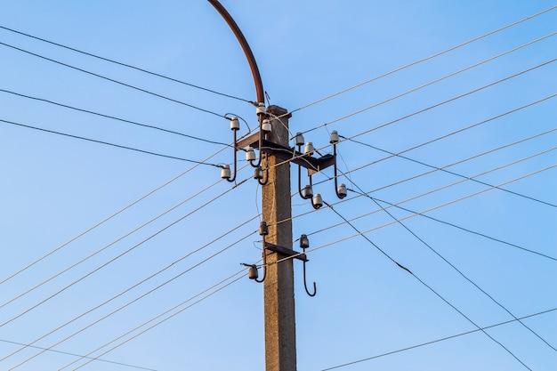 De lijnen en de draden van elektrische poolmacht met blauwe hemel