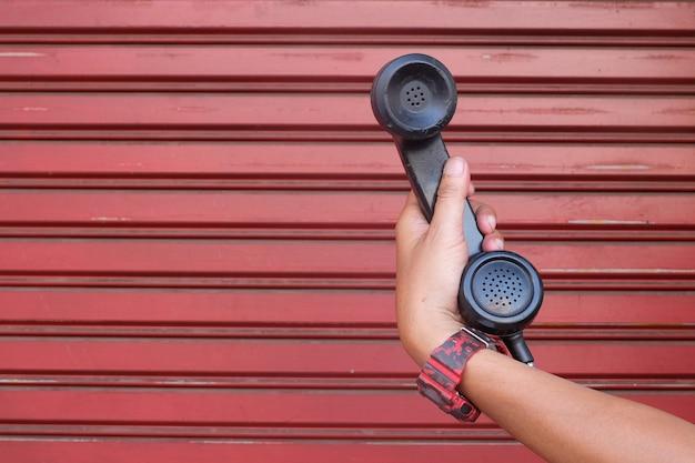 De linkerhand houdt de telefoon vast en de achterdeur is rood