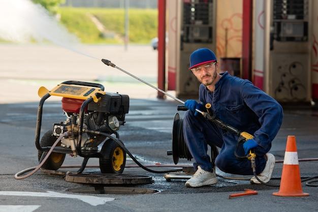 De loodgieter bereidt zich voor om het probleem in het riool op te lossen. reparatiewerkzaamheden bij het oplossen van problemen.