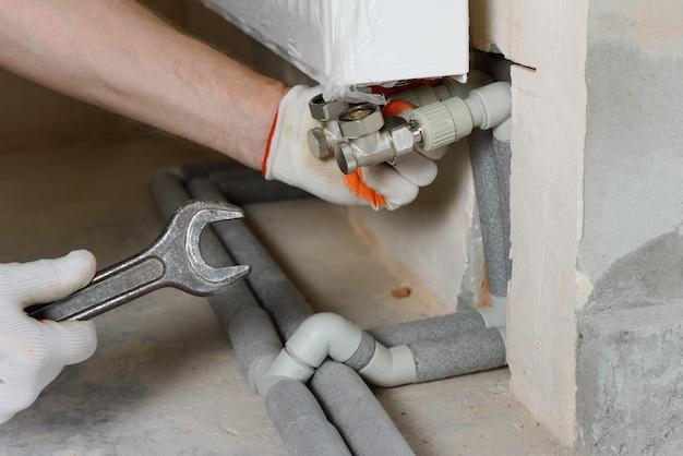 De loodgieter bevestigt de leidingen van het verwarmingssysteem aan de radiator