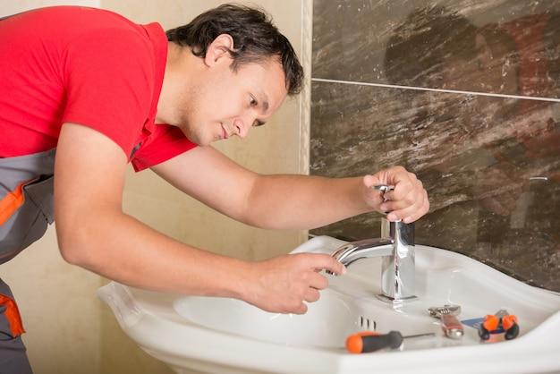 De loodgieter herstelt een kraan met water in de badkamers