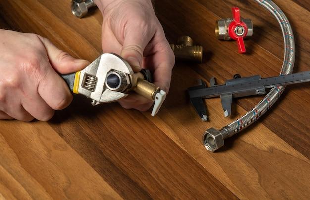 De loodgieter schroeft de messing fitting op de klep met een sanitaire sleutel