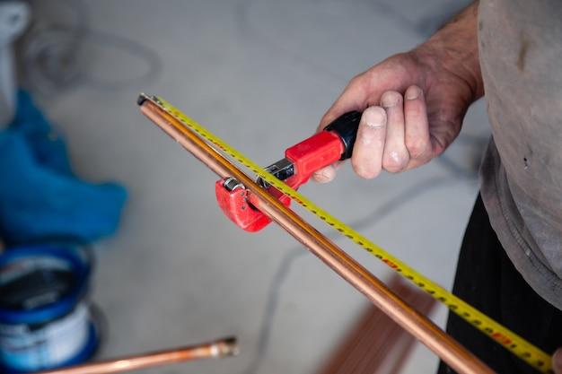 De loodgietermeester van de close-uparbeider meet koperpijpen met rouletteband, snijd pijp met snijder.