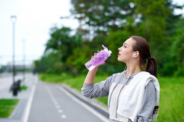 De lopende aziatische vrouw heeft onderbreking, drinkwater tijdens looppas in de zomerpark
