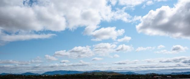 De lucht en de open ruimte met bergen eronder. wolken die boven de bergen zweven.