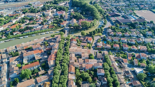 De lucht hoogste mening van woonwijk herbergt daken, straten en kanaal met hierboven boten, oude middeleeuwse stadsachtergrond, frankrijk