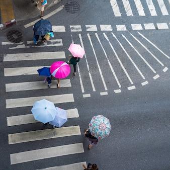 De luchtfoto hoogste mening van mensen loopt op straat in de stad over voetgangersoversteekplaatsverkeersweg