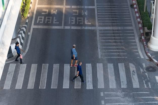 De luchtmeningsfoto van mensen loopt op straat in de stad over voetgangersoversteekplaatsverkeersweg