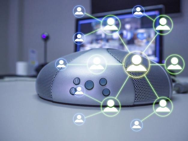 De luidsprekertelefoon en videoconferentie in vergaderruimte met mensennetwerkpictogram dat het idee voor nieuw normaal werken vertegenwoordigt.