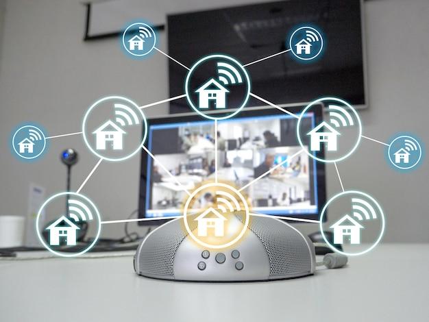 De luidsprekertelefoon en videoconferentie in vergaderruimte met thuisnetwerkpictogram dat het idee voor nieuw normaal werken vertegenwoordigt.