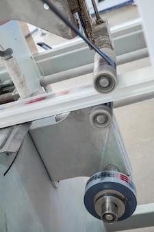 De machine lijmt het lint met de print op de profielproductie van pvc-profiel