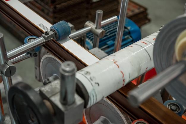 De machine lijmt het lint met de print op het profiel productie van pvc-profiel