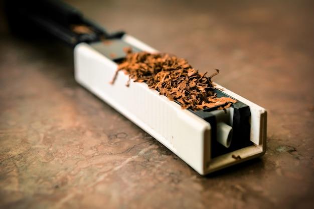 De machine om sigaretten met tabak te vullen. leeg zuchtig. rossypany-tabak op de tafel. zelfgemaakte sigarettenproductie