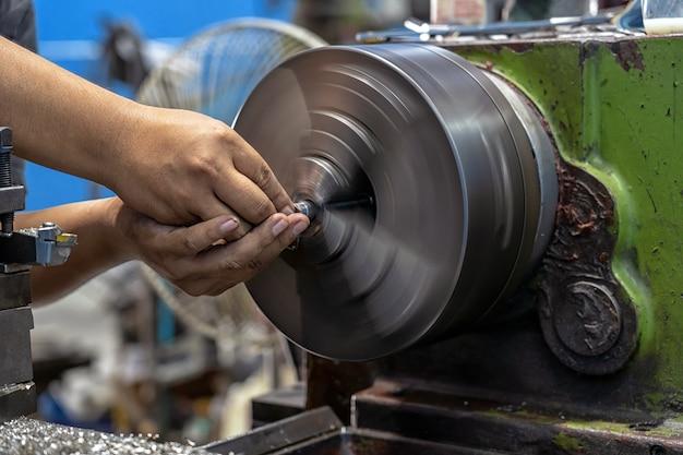 De machinisthand die van de close-up met draaibankenmachine werkt in metaalbewerkingsfabriek
