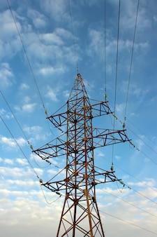 De machtslijnen van de afhankelijkheid met kabels op blauwe hemel met wolken.