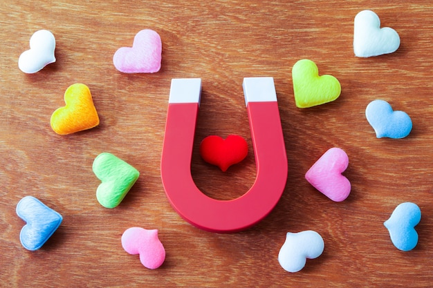 De magneet graviteert hartvorm op houten achtergrond, liefdeconcept
