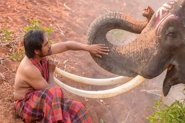 De mahout zit bij de olifant.