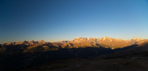 De majestueuze toppen van het nationale park massif des ecrins (4101 m) met de gletsjers, in frankrijk, bij zonsopgang. heldere lucht, herfstkleuren.
