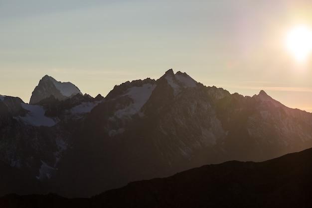 De majestueuze toppen van het nationale park massif des ecrins (4101 m) met de gletsjers, in frankrijk. telelensweergave van verre bij zonsopgang. heldere lucht, herfstkleuren.
