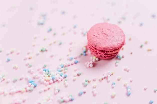 De makaron met kleurrijke pastelkleur bestrooit over roze achtergrond
