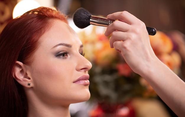 De make-upkunstenaar die vloeibare toon- stichting op het gezicht van de vrouw in wit toepassen maakt omhoog ruimte. schoonheid en mode.