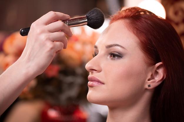 De make-upkunstenaar die vloeibare toon- stichting op het gezicht van de vrouw in wit toepassen maakt omhoog ruimte.