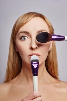 De make-upkunstenaar van de vrouw houdt make-upborstels dichtbij gezicht.