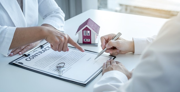 De makelaar wijst met zijn hand en legt het zakelijke contract, de huur, de aankoop, de hypotheek, een lening of de woningverzekering uit aan de mannelijke koper.