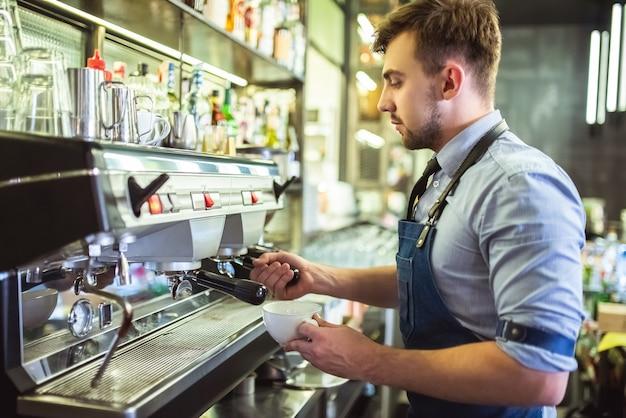 De man aan het werk met een koffiezetapparaat aan de bar