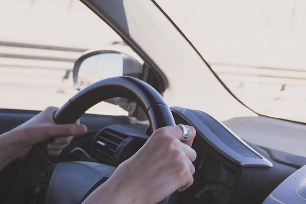 De man achter het stuur van een auto. vrouwelijke handen op het stuur van een auto tijdens het rijden.