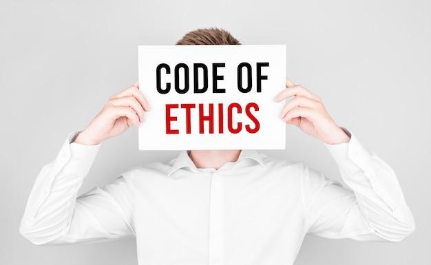 De man bedekt zijn gezicht met een wit papier met de tekst code of ethics