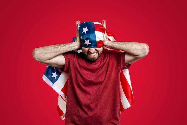 De man bedekt zijn oren en ogen met een amerikaanse vlag.