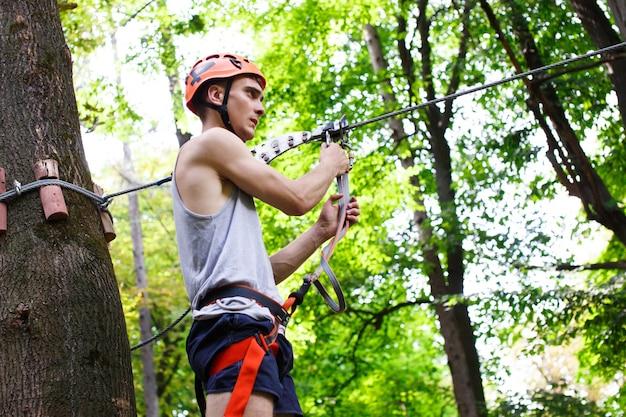 De man bereidt zich op de touwtjes in het park te beklimmen