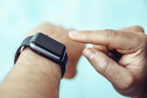 De man bestuurt door met zijn vinger een slim horloge op zijn hand aan te raken
