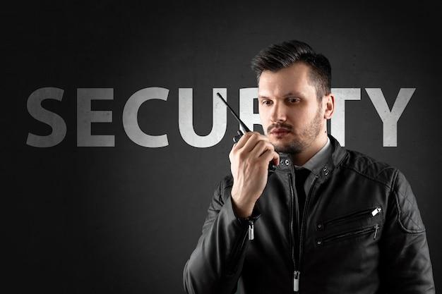De man, beveiliging, houdt een walkietalkie vast