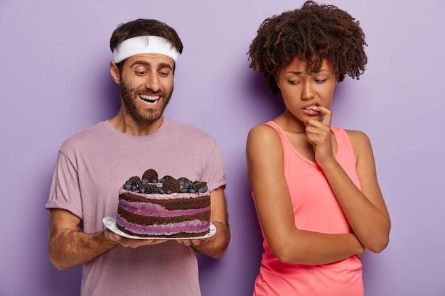 De man biedt zijn vrouw heerlijke cake aan. verbaasde afro-amerikaanse vrouw keert terug naar haar echtgenoot, kijkt met verleiding naar zoet dessert, vermijdt junkfood om fit te blijven, draagt sportkleding. afslanken, calorieën
