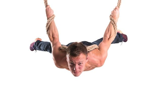 De man die aan de touwen hangt met een gespannen uitdrukking op zijn gezicht geïsoleerd op een witte achtergrond